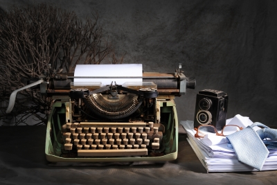 typewriter on a table with an old camera and ream of paper