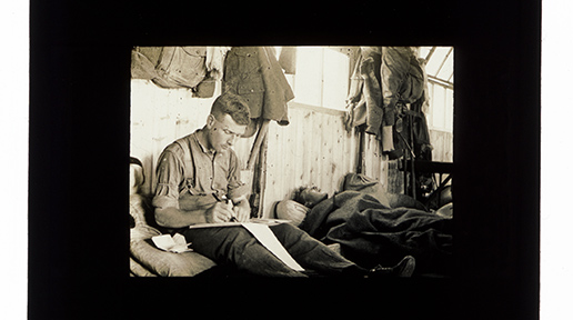 """""""Randalstown Camp, Co. Antrim, 1915. Hackney's friend John Ewing from Belfast writes in a diary or a letter home, while his comrade lies sleeping in his bunk. Ewing was later promoted to sergeant and won the Military Medal for bravery in the field."""" - Secretly Photographed World War I"""