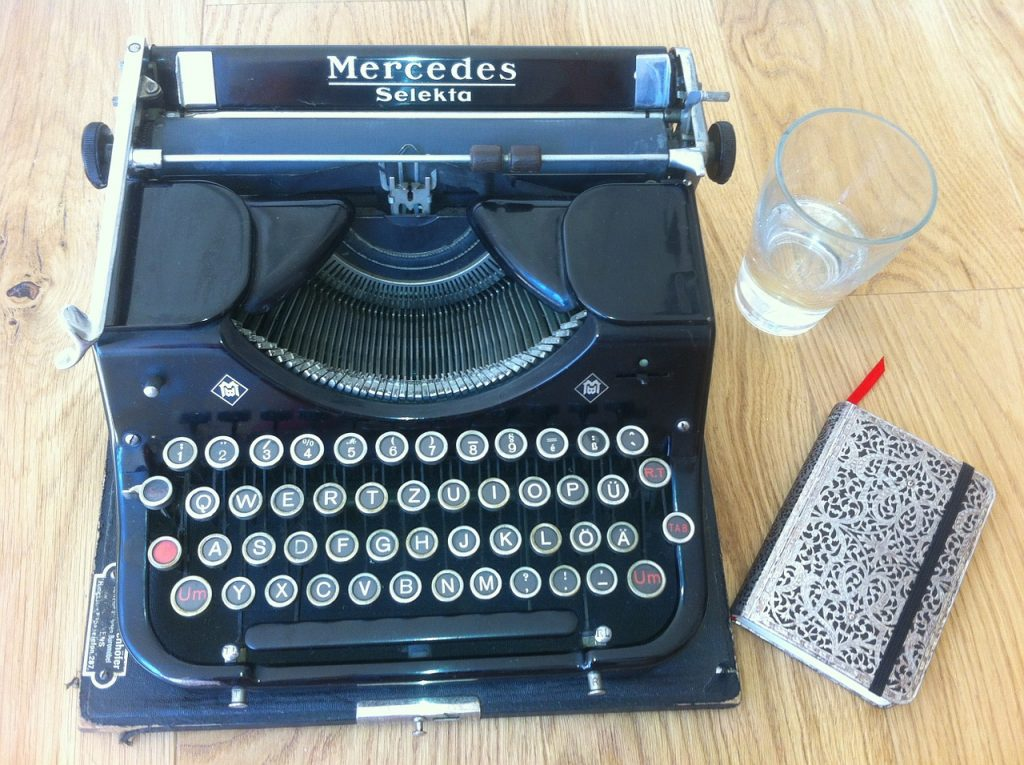 A Mercedes Selekto antique type writer sites on a blonde wood table with a glass of water and small notebook. grammar, writing