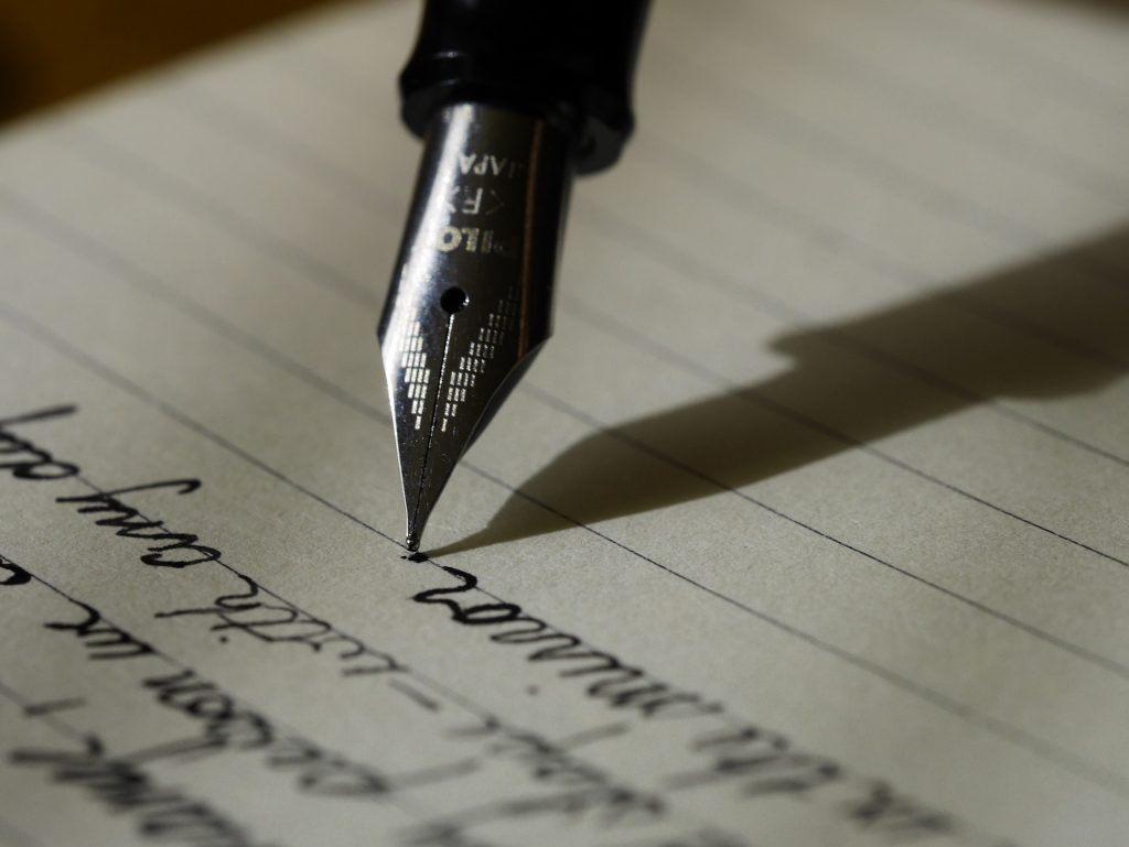 an old ink pen scribbles words on a lined page, writing, grammar