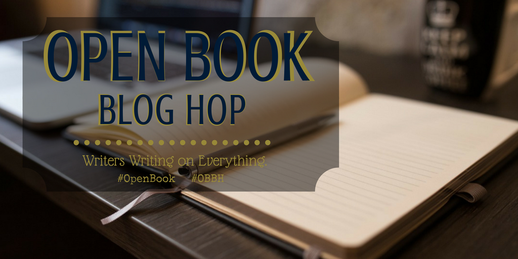 Open Book Blog Hop banner over a desktop with a notebook and pen.
