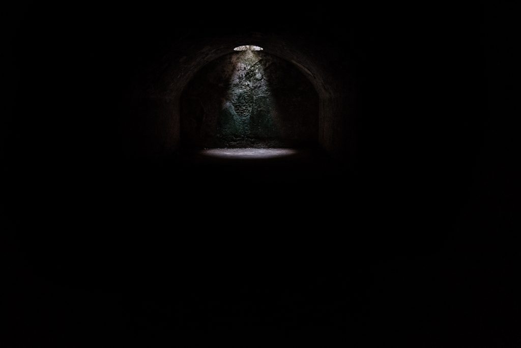 Dark, underground tunnel with a dim light highlighting the background.