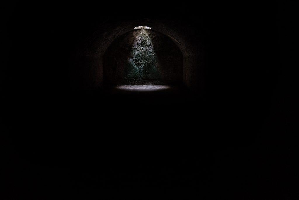 Dark, underground tunnel with a dim light highlighting the background.