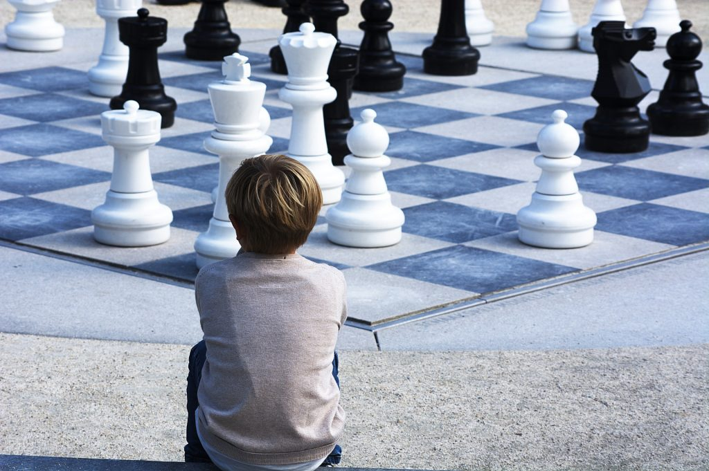 A young person sits before a giant chess board contemplating it, book boss