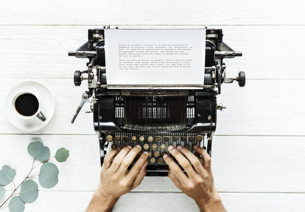 hands hover over the keyboard of an antique typewriter, with a cup of coffee on the side, and page partially full of courier typeface. write no matter what