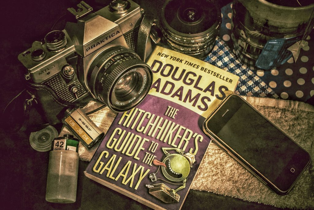 towel day, douglas adam's well-known book, HitchHiker's Guide to the Galaxy is on a table surrounded by an old camera and cell phone