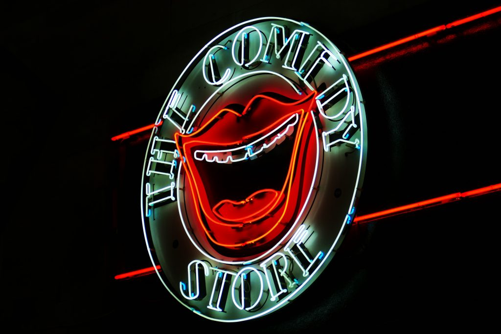 open book blog hop, neon light depicting a laughing mouth, the words The Comedy Store surrounding it.