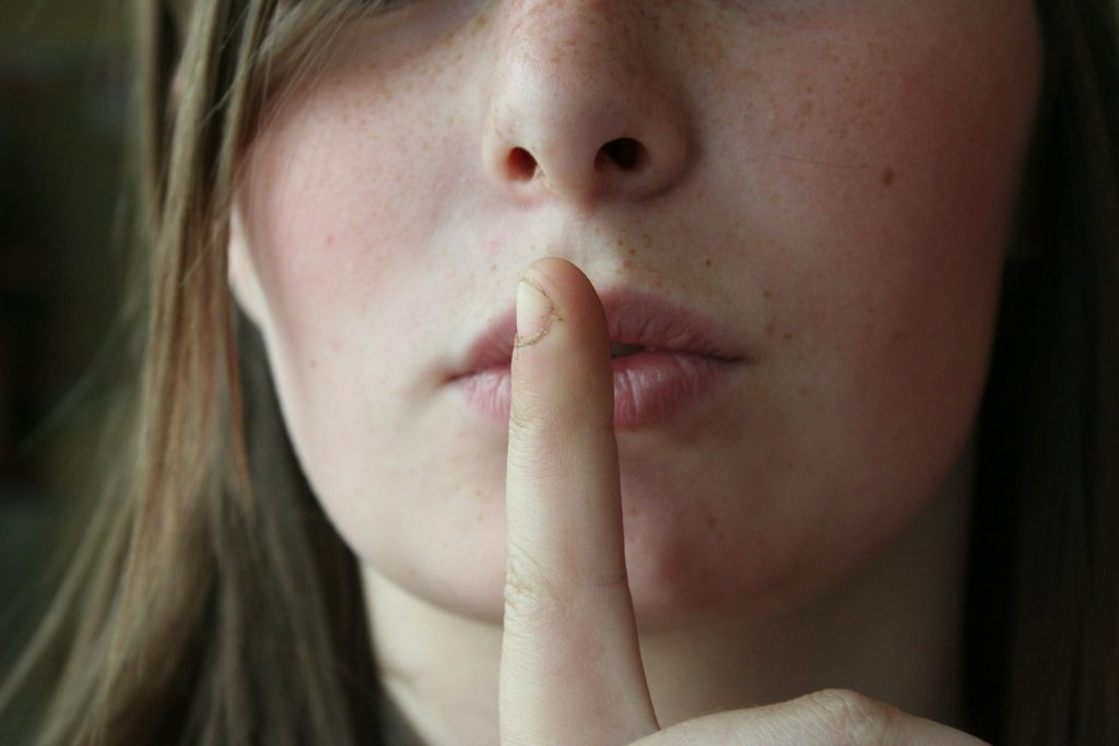 woman with her finger pressed to lips