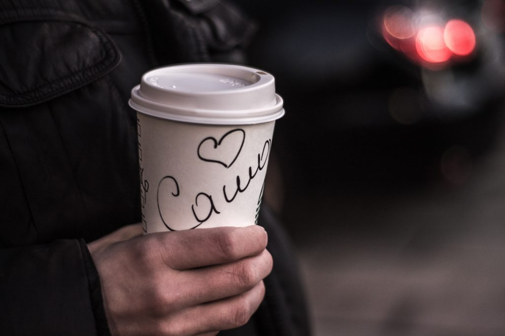 hand with coffee cup, scrawled with name on it.