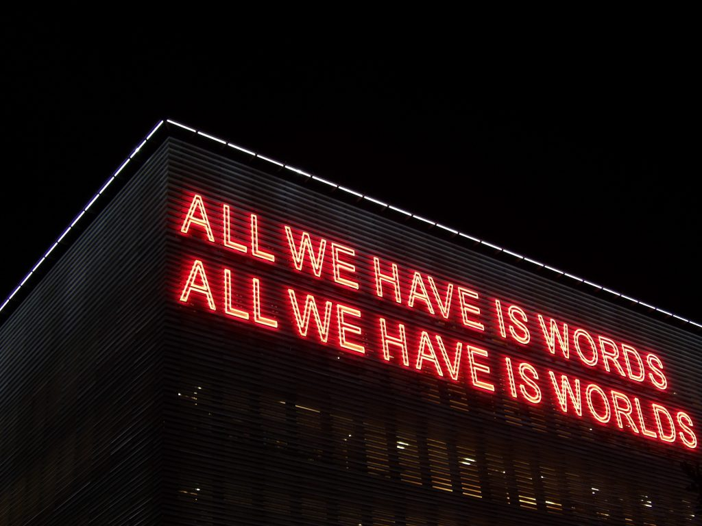 neon sign that reads: All we have is words. All we have is worlds.