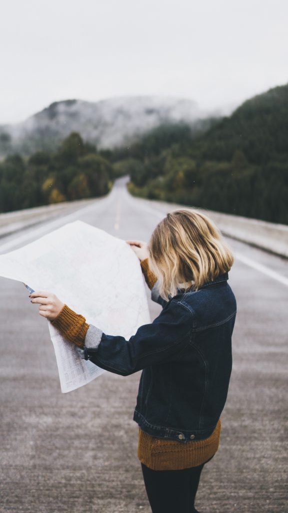 girl on a mountain road with a map