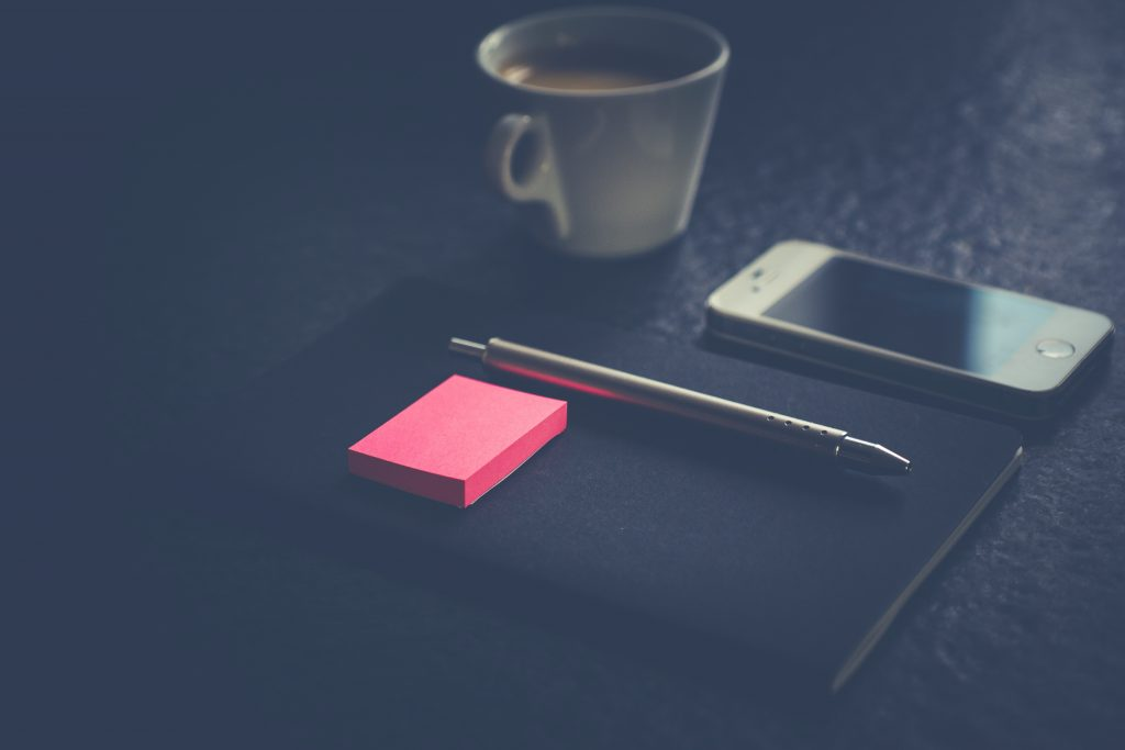 black table top with a notebook, post it notes, a pen, phone and cup of coffee.