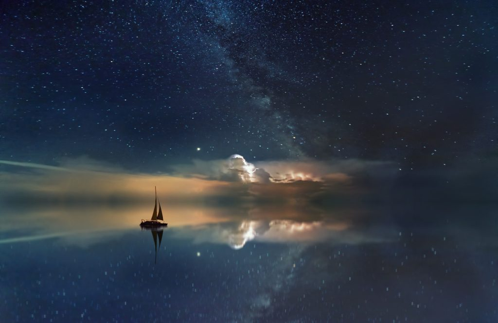 still ocean with a boat sailing toward a starry sky that seems to bleed into the water