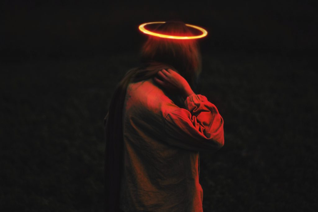 person standing in the dark with a halo over their head.