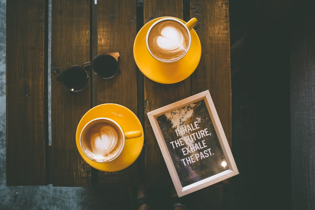 table top with two cups of coffee, cream hearts in the cup, and a tablet on the table that reads: inhale the future, exhale the past.