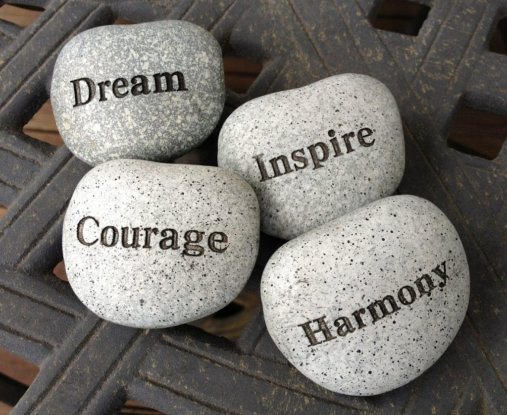four round stones that say dream, courage, inspire, harmony