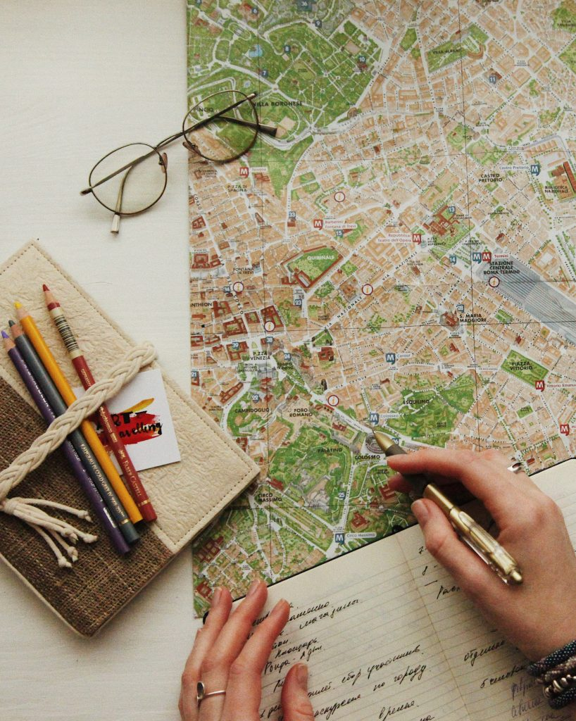 a map lies on the table with books and writing implements, as a person takes notes. Photo by Oxona on Unsplash