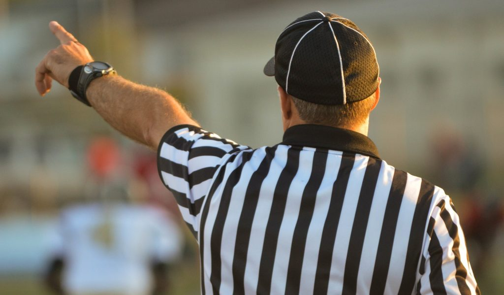 mid shot, back of a referee signaling a foul, sport image