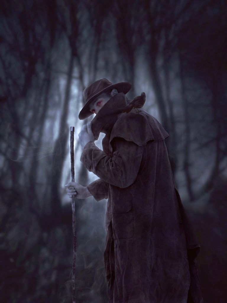 A nephilim trying to hide his face as he walks through the wood. His red eyes are quite distinct. Image by Syaibatul Hamdi from Pixabay