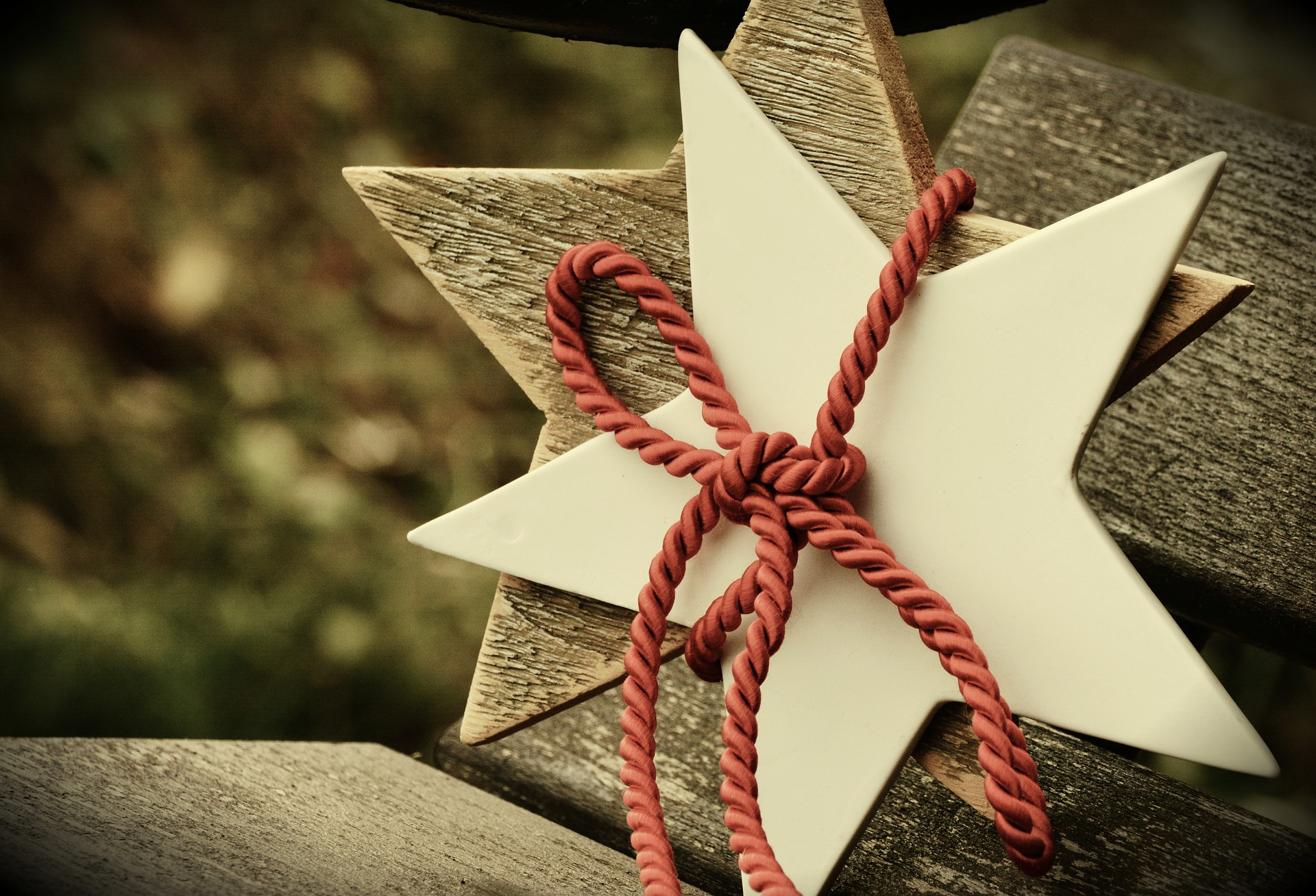 pixabay stock photo, white paper star tied to a wooden cut out star with red string.